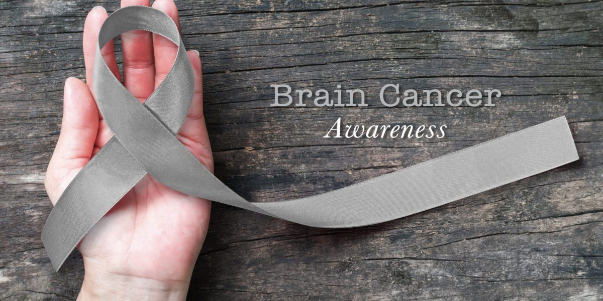 Brain cancer awareness, grey ribbon on helping hand
